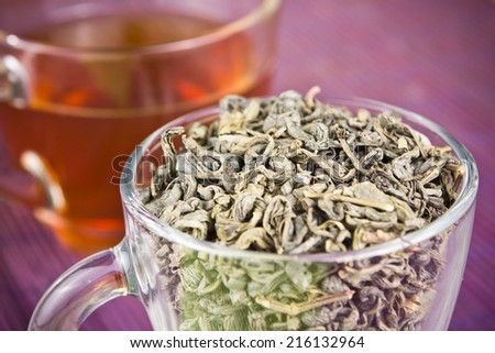 Green tea leaves in glass on violet bamboo mat. - stock photo