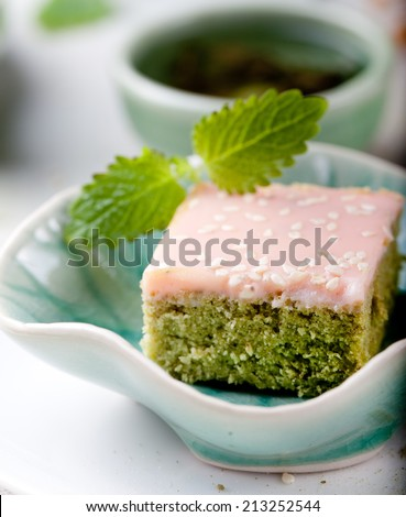 Green tea, matcha cake with white chocolate and sesame seeds glaze with a cup and tea pot on a wooden background. - stock photo
