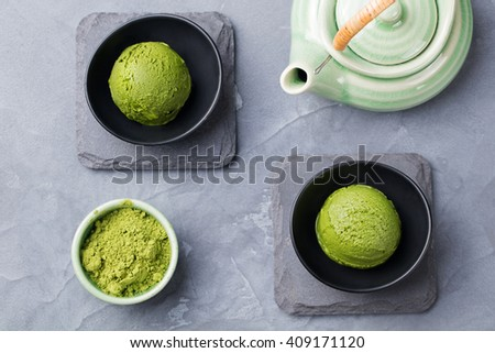 Green tea matcha ice cream scoop in bowl on a grey stone background Top view - stock photo