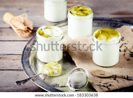 Green tea matcha yogurt, dessert, mousse in glass jars on a vintage metal tray on a wooden background - stock photo