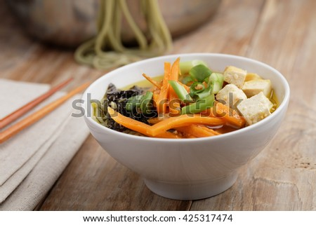 Green tea noodle soup with tofu and vegetables - stock photo