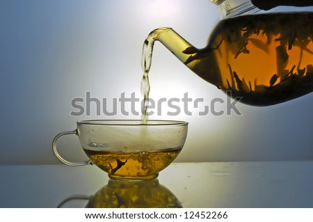 Green tea pouring into glass cup from teapot on blue background
