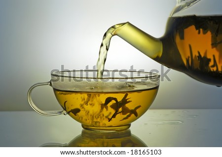 Green tea pouring into glass cup from teapot on blue background - stock photo
