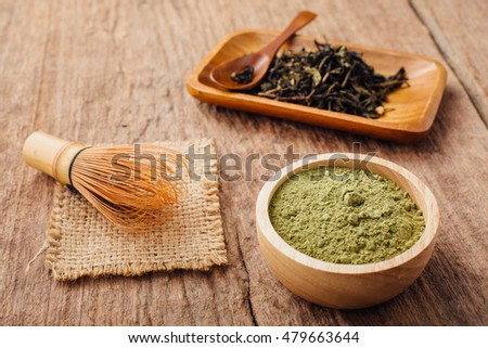 green tea powder and dried tea leaves on wooden background