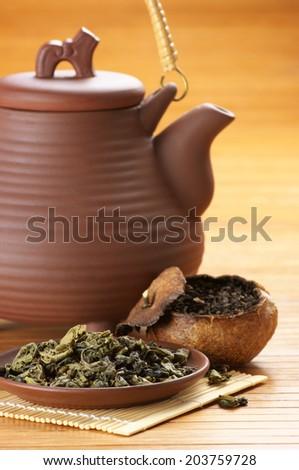 Green tea, pu-erh tea aged in mandarin and ceramic teapot. - stock photo