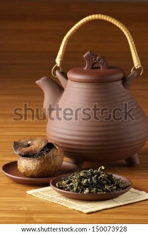 Green tea, pu-erh tea aged in tangerine and ceramic teapot. - stock photo
