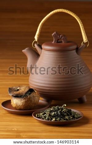 Green tea, pu-erh tea aged in tangerine and ceramic teapot. Focus on foreground. - stock photo