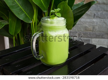 Green tea smoothies on wood table. selective focus - stock photo