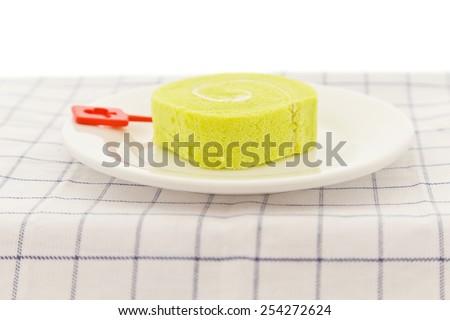 Green tea swiss roll cake on white dish. - stock photo