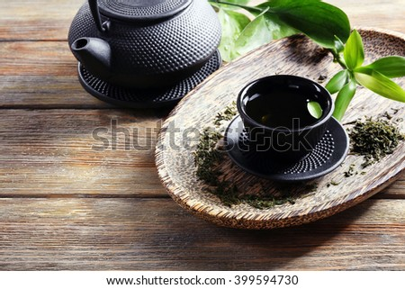 Green tea with black utensils on wooden table - stock photo
