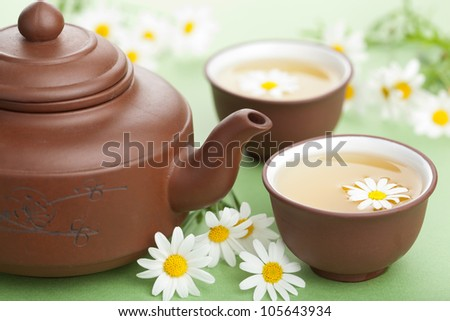 green tea with chamomile flowers - stock photo