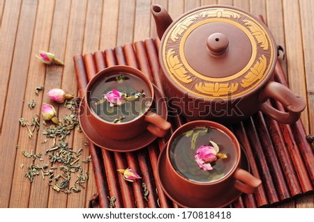 Green tea with dry roses and the Chinese teapot  - stock photo