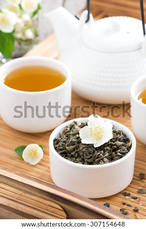 green tea with jasmine and kettle of freshly brewed tea, vertical - stock photo