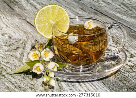 Green tea with jasmine and lemon on a wooden table. - stock photo
