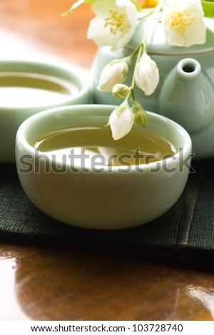 Green tea with jasmine in cup and teapot on wooden table - stock photo