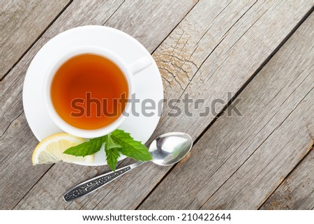 Green tea with lemon and mint on wooden table background with copy space - stock photo