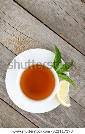 Green tea with lemon and mint on wooden table background with copy space