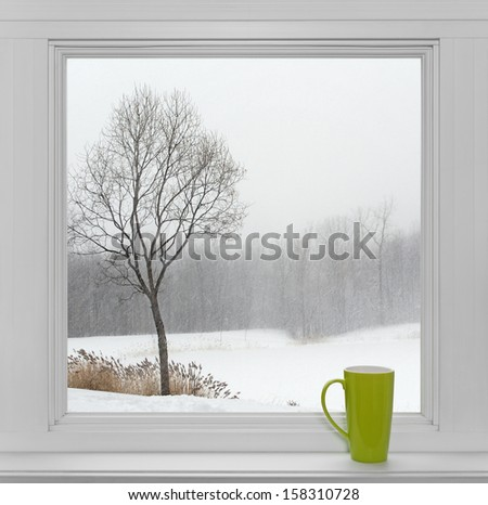 Green teacup on a windowsill, with winter landscape seen through the window. - stock photo