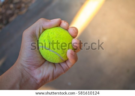 Green tennis ball in hand.