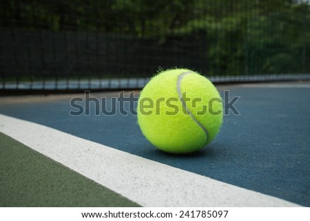 green tennis ball next to the line of the tennis court