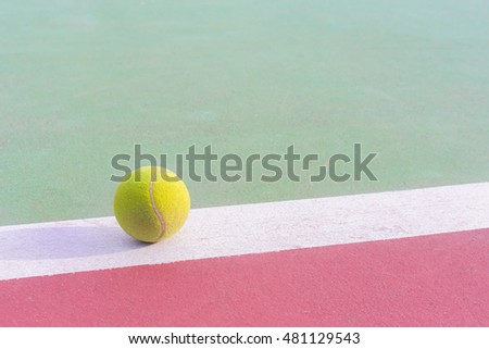 green tennis ball on white line of tennis court