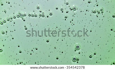 Green texture of a liquid with bubbles. Green water with bubbles. Closeup - stock photo