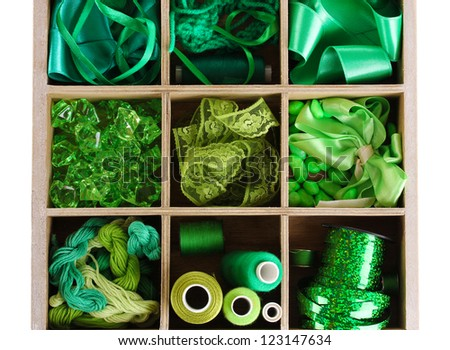 Green thread and material for handicrafts in box isolated on white - stock photo
