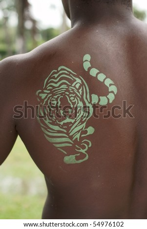 green tiger painted on the back of an african descendant man - stock photo
