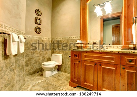 Green tile wall trim. View of gold vanity with large mirror