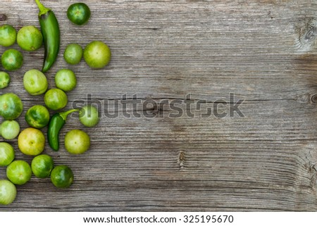 green tomatoes and peppers on wooden background with copy space