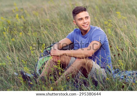 Green tourism.  Portrait of a young handsome tourist wearing blue t-short and beige shorts, sitting on the plaid looking aside smiling - stock photo