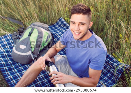 Green tourism.  Top view of a young handsome tourist wearing blue t-short and beige shorts, sitting on the plaid drinking tea from thermos , backpack near - stock photo