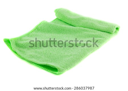 Green towel folded in the shape of a square on a white background