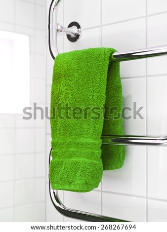 Green Towel on a dryer in modern bathroom environment - stock photo