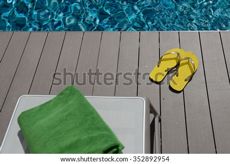 Green tower and yellow flips flops beside swimming pool - stock photo