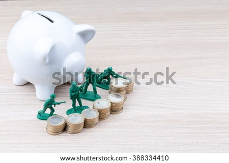 Green toy soldiers in front of piggy bank, a concept for keeping money secure or a defensive investment - stock photo