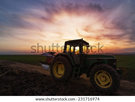 Green tractor on field at sunset after plowing - stock photo