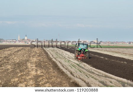 green Tractor Plowing in Autumn - stock photo