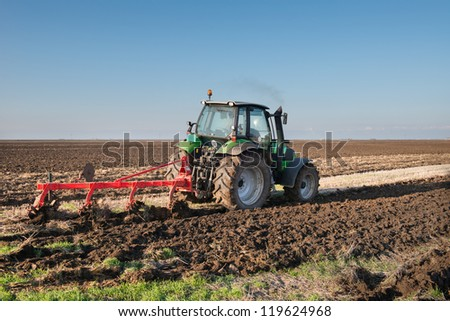green Tractor Plowing in Autumn