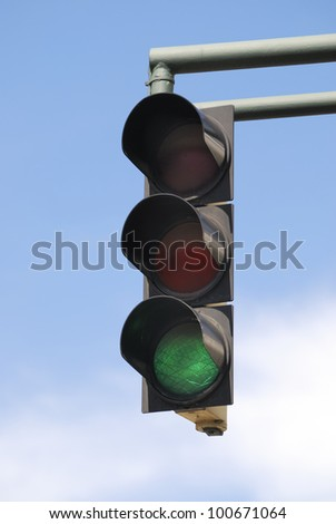 Green traffic light and blue sky