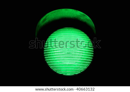 green traffic light, isolated on black background - stock photo