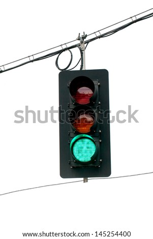 Green traffic light swinging from wires overhead.  Close up with white background. Vertical - stock photo