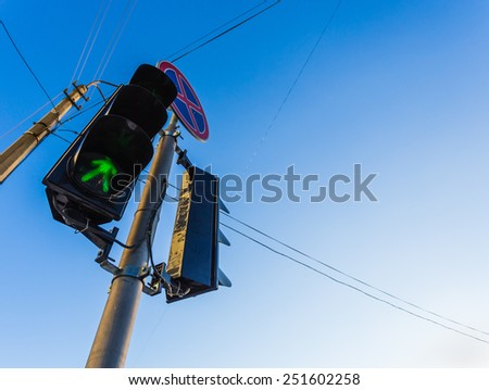 Green traffic light with sign and wires - stock photo