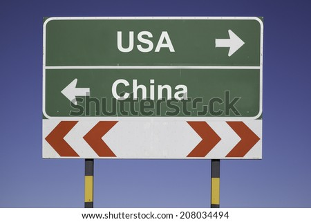 green traffic sign in front of a blue sky, horizontal arrows showing two directions and a red white road warning post. Business concept for the relations or conflicts between two Nations: USA, China - stock photo