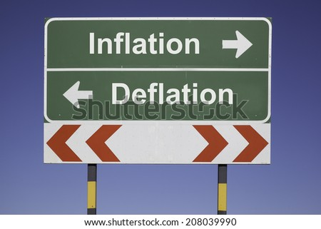 green traffic sign in front of a blue sky, horizontal arrows showing two directions and a red white road warning post. Business fiscal concept for financial trends: Inflation and deflation - stock photo