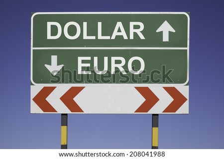 green traffic sign in front of a blue sky, horizontal arrows showing two directions and a red white road warning post. Business fiscal concept for currency exchange rate,  Dollar up and Euro down - stock photo