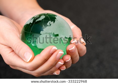 Green transparent earth globe in the hand with Earth saving concept.