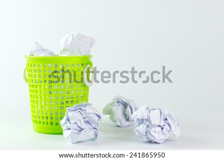 Green trash bin and crumpled paper balls on white background - stock photo