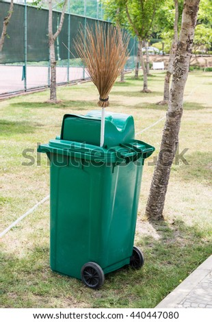 Green trash can and coconut stick broom on the field near the tennis court. - stock photo