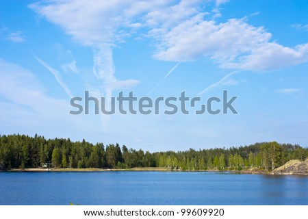 Green trees by the lake on a sunny day, with clouds on the sky - stock photo